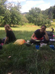 Fotka dvou účastnic expedice sedících u oběda v trávě